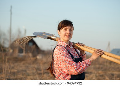 Happy female farmer  with spade and pitchfork in rural