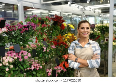 Happy female florist standing in flower shop