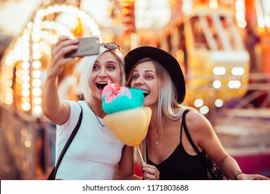 Happy female friends in amusement park eating cotton candy and taking selfie.Two young women enjoying a day at amusement park.