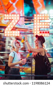 Happy female friends in amusement park eating cotton candy. Two young women enjoying night at amusement park.
