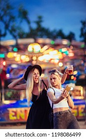 Happy female friends in amusement park taking selfie. Two young women enjoying night at amusement park.
