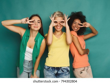 Happy female friends in colourful clothes having fun at blue background. Three young women posing, showing different signs and laughing, slumber party, copy space