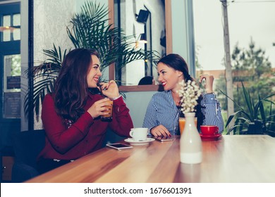 Happy female friends talking and drinking coffee while looking each other sitting in the table in a cafe.