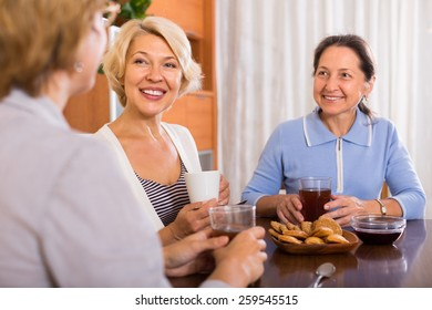 Happy female friends talking during tea drinking at home. Focus on blonde