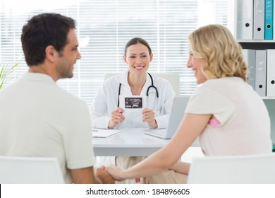 Happy female gynaecologist looking at expectant couple in clinic
