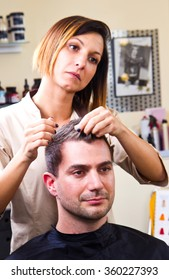 Happy female hairstylist setting client's hair