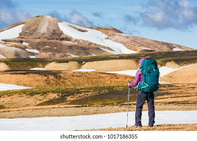 Happy female hiker with backpack enjoying the landscape of Iceland while hiking the Laugavegur trail. Travel, sport, lifestyle concept