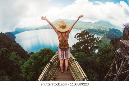 Happy female hiker standing on a cliff with her arms up in the air feeling free. Active healty concept