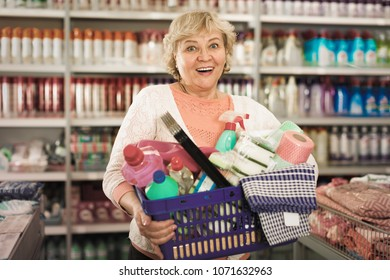Happy female holding basket with goods for cleaning house in the household chemical shop