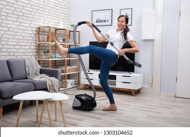 Happy Female Janitor Dancing With Vacuum Cleaner At Home