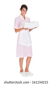 Happy Female Maid Holding Stack Of White Towels Over White Background