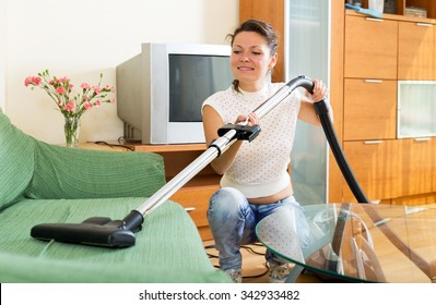 Happy female make cleaning at house using hoover