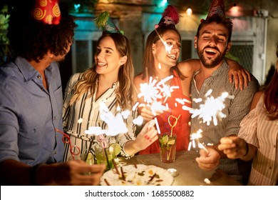 Happy female and male holding sparkles on birtday party