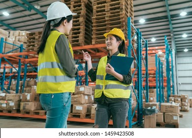 Happy female manager and worker standing together in warehouse office. two women staff in storehouse discussing cooperation. young girls employees wearing hard hats and safety vest in stockroom.