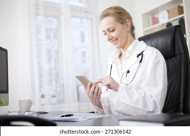 Happy Female Medical Doctor Sitting at her Table and Browsing Something on her Mobile Phone