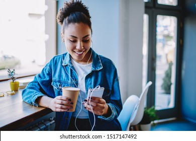 Happy female meloman typing name of song for search and download from multimedia application on cellular phone during coffee time in cafeteria,positive hipster girl listening audio book via headphones