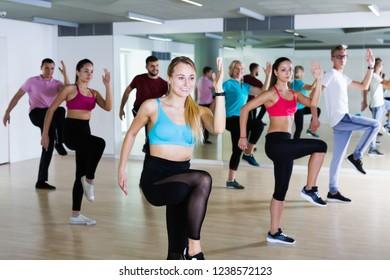 Happy female and men dancing together in dance studio