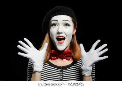 Happy female mime on black background. Cute actress is using exaggerated face expressions, hand gestures and no words in acting a pantomime.