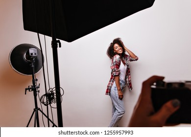 Happy female model with cheerful smile looking at photographer. Indoot shot of amazing african woman smiling during professional photoshoot.