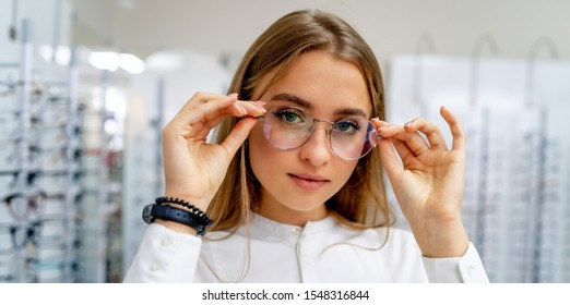 Happy female optometrist, optician is standing with set of glasses in background in optical shop. Stand with spectacles. Girl wearing glasses. Portrait of a woman in correcting glasses.
