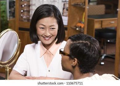 Happy female optometrist with patient looking at mirror
