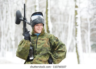 happy female paintball extreme sport player wearing protective mask and comouflage clothing with marker gun at winter outdoors