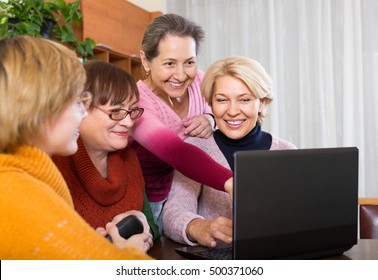 Happy female pensioners working with notebook using wifi