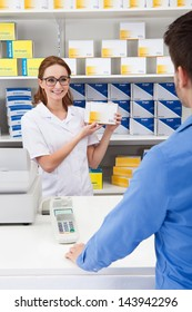 Happy Female Pharmacist Showing Drug In Pharmacy To Client