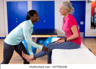 Happy female physiotherapist giving leg massage to active senior woman in sports center. Sports Rehab Centre with physiotherapists and patients working together towards healing