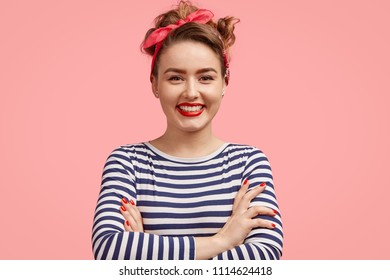 Happy female with positive expression, keeps hands crossed, dressed in striped jacket and stylish headband, poses against pink background, glad to see her photo on poster. People and emotions