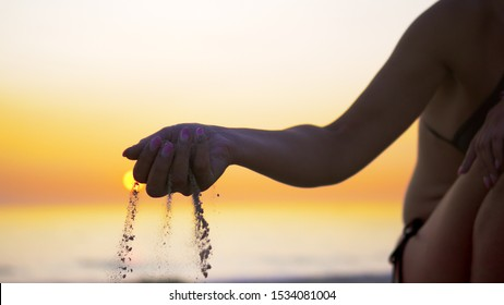Happy female pours sand from the hand on sea beach sunset, concept of vacation, freedom, happiness, nature, travel