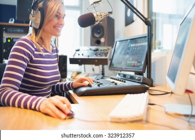 Happy female radio host using computer while broadcasting in studio