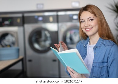happy female reading book while doing her washing in laundromat