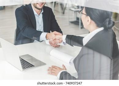 Happy female shaking man hand
