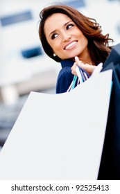 Happy female shopper smiling and carrying bags