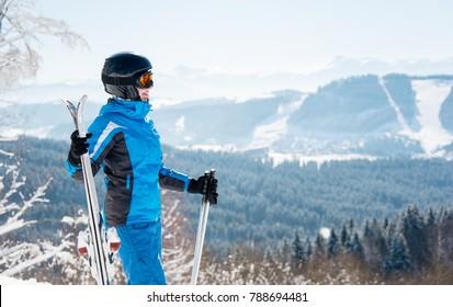 Happy female skier enjoying stunning scenery in the winter mountains ski resort, looking away, holding skis, wearing blue ski suit and black helmet copyspace