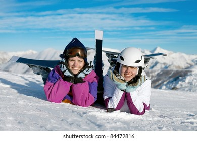 Happy female skiers resting in the snow