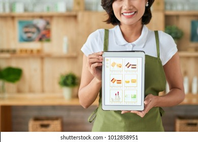 Happy female small business woner showing tablet with website of her handmade soap shop on the screen