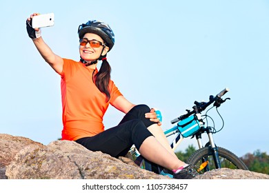 Happy female smiling cyclist taking a selfie photo outdoor.