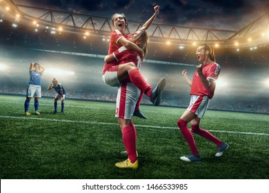 Happy Female Soccer players on a professional soccer stadium. Girls Team emotionally celebrates victory