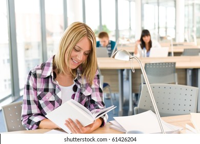 Happy female student with book in classroom, schoolmates in background