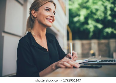 Happy female student with cute smile on face studying information notes learning at outdoors table desktop, cheerful Caucasian woman 20 years old enjoying accounting with education textbook