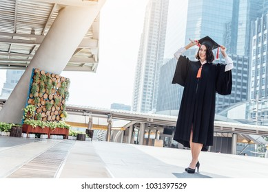 Happy female student graduate is standing and waiting friend with diploma in hand. Dreaming about future success.