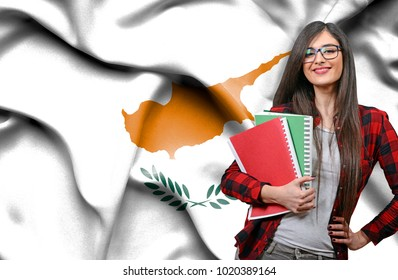 Happy female student holdimg books against national flag of Cyprus