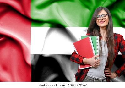 Happy female student holdimg books against national flag of United Arab Emirates