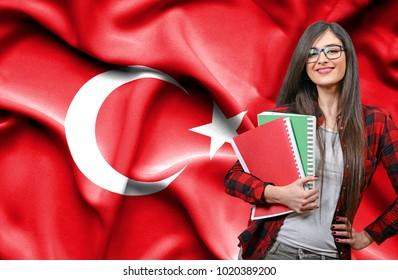 Happy female student holdimg books against national flag of Turkey
