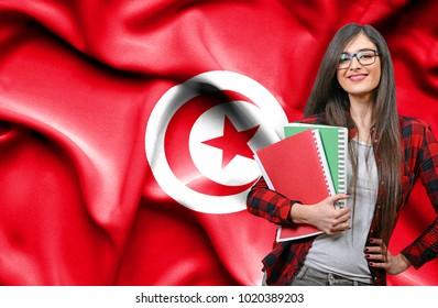 Happy female student holdimg books against national flag of Tunisia