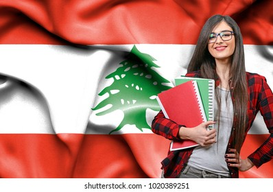 Happy female student holdimg books against national flag of Lebanon