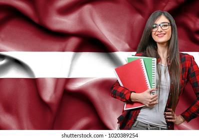Happy female student holdimg books against national flag of Latvia
