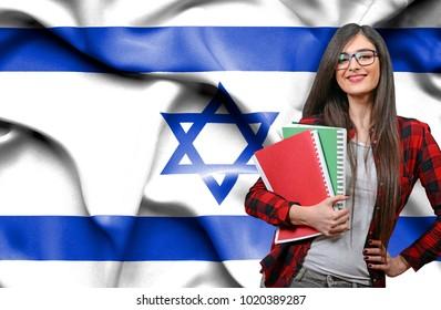Happy female student holdimg books against national flag of Israel